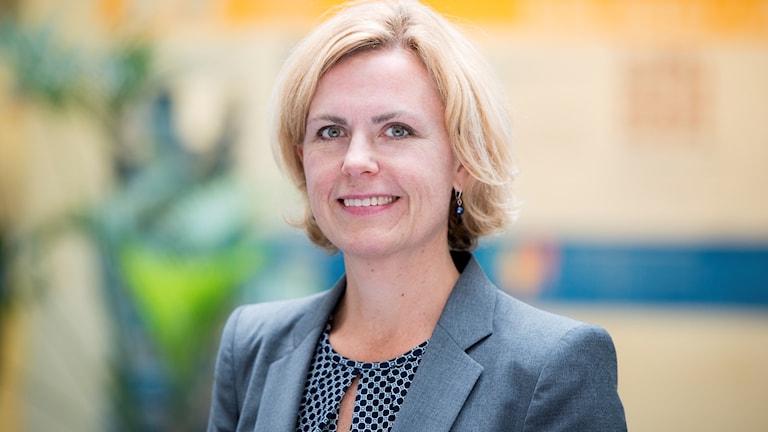 En kvinna med blont hår i page, klädd i blå kavaj.
