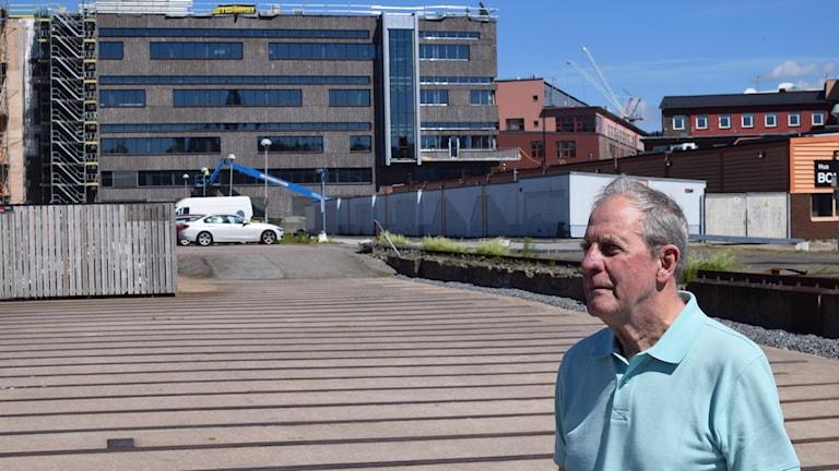 En man står utomhus framför en byggnad.