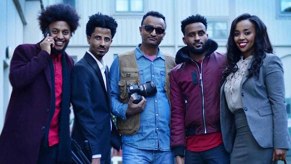 Fem personer med mörkt hår står uppradade bredvid varandra och ler mot kameran.