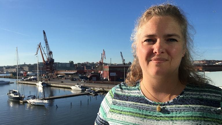 Maria Taranger står på en balkong i Kanalhuset, med Göta älv och flera segelbåtar i bakgrunden.