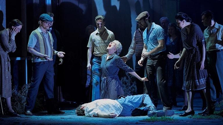 pressbild från operan. folk står runt en person som ser ut att ha fallit död ner. en operasångare skriker.