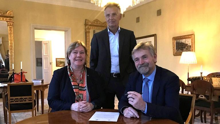 tre glada personer vid ett bord