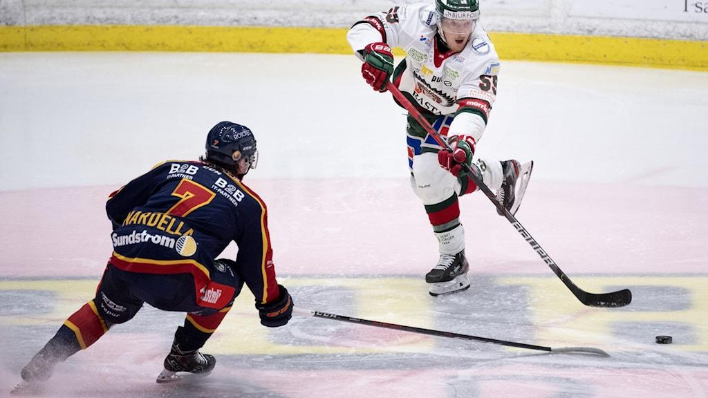Två hockeyspelare på is.
