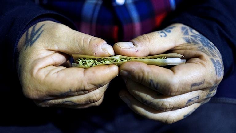 Två händer som rullar en joint.