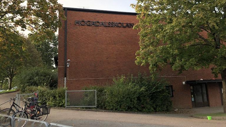 En avlång låg skolbyggnad i brunröd-färgat tegel.