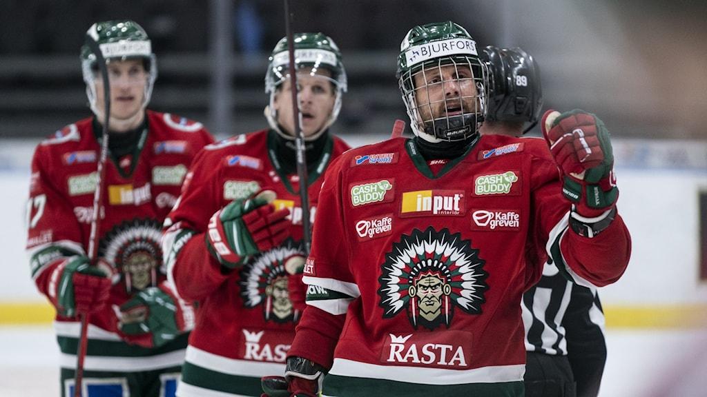 Tre frölundaspelare i röda ishockeytröjor på isen.