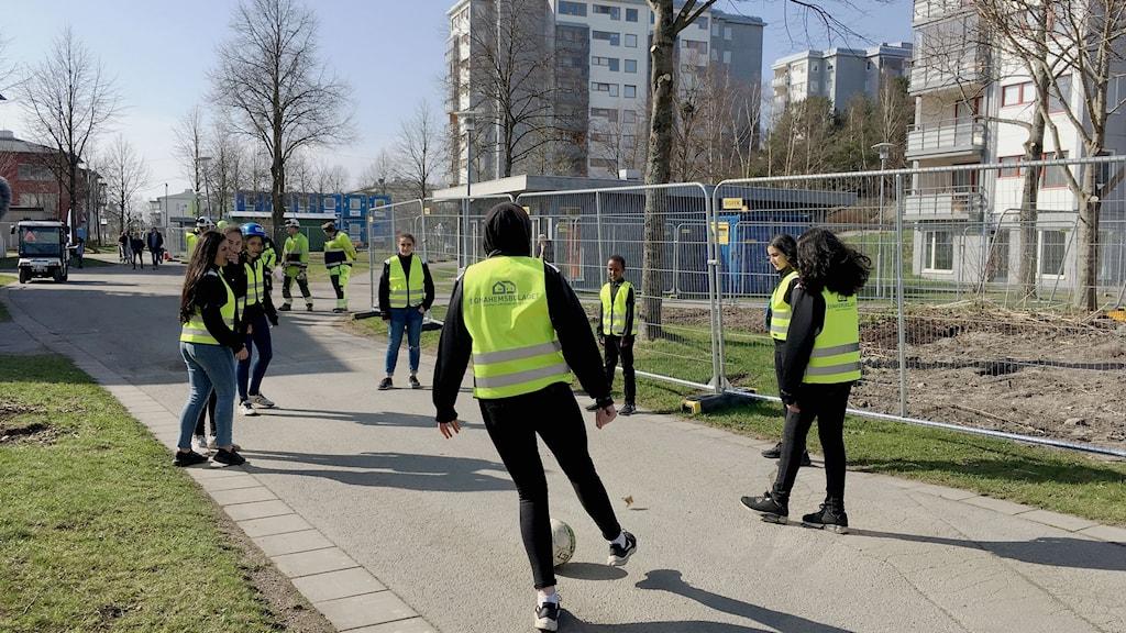 En grupp tjejer sparkar boll mellan husen i Lövgärdet.