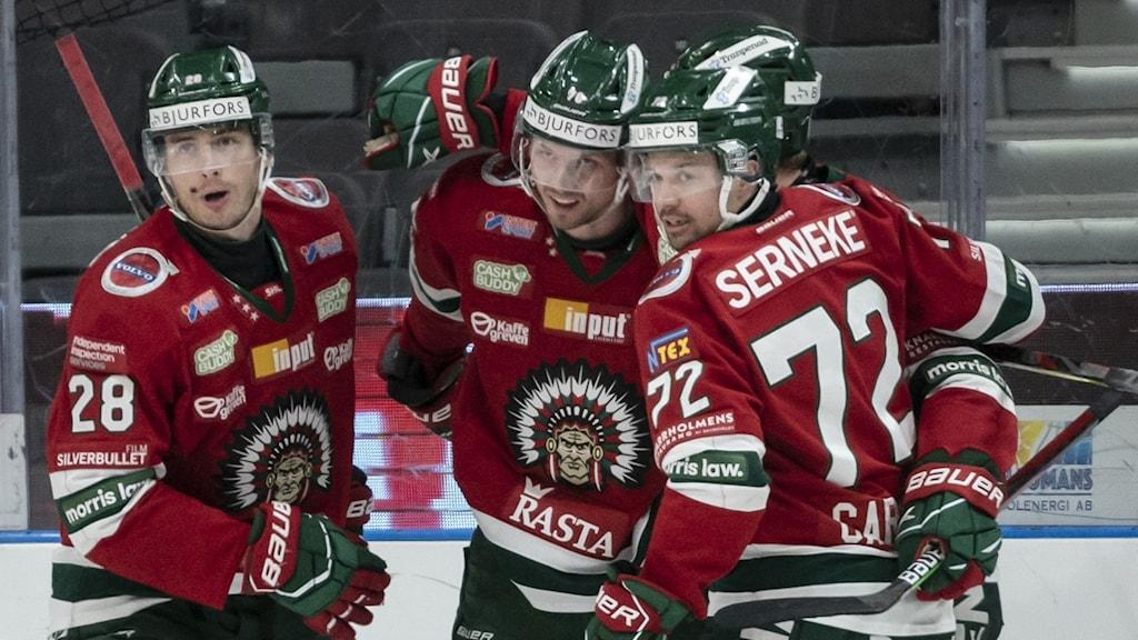 fyra hockeyspelare firar ett mål ute på isen