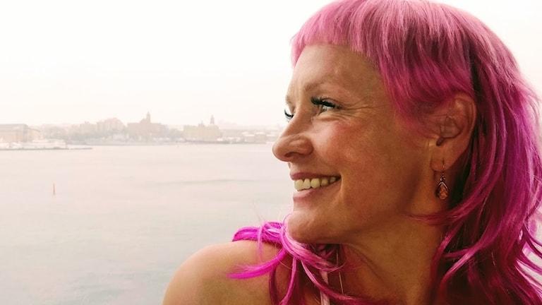 En kvinna med rosafärgat hår med Götaälv i bakgrunden.