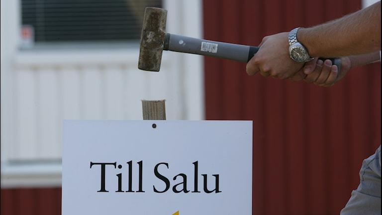 """En person slår ner en """"Till Salu""""-skylt i marken med en hammare"""