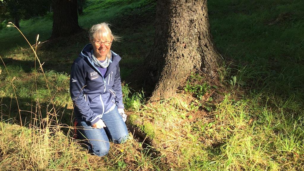 Kvinna sitter i skog