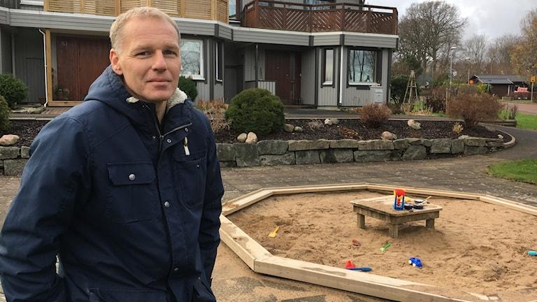 En man står vid en sandlåda på platsen där hans barndomshem låg.