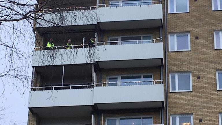 Ett gult höghus. På en av balkongen står personer i varselkläder.
