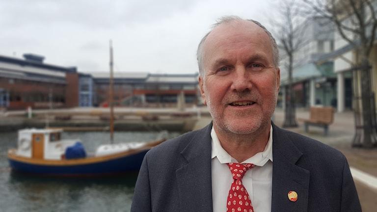 Bo Pettersson står framför en fritidsbåt med segel.