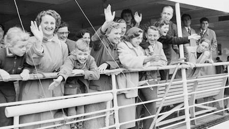 Människor står och vinkar vid relingen på ett fartyg.