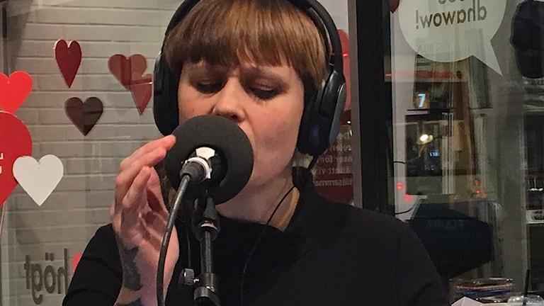 En kvinna med brunt hår och hörlurar sjunger i en mikrofon.