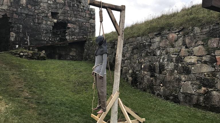 En docka föreställande en man hänger i avrättningsgalge.