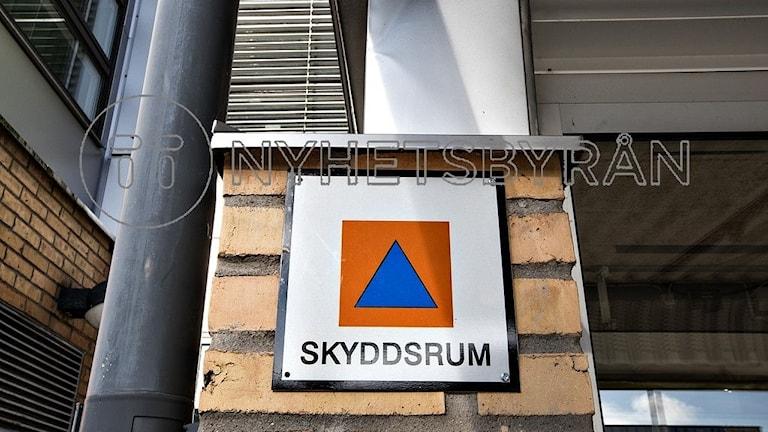 Skylt som markerar ett skyddsru. Vit skylt med orange kvadrat med en blå triangel i och textnr skyddsrum.