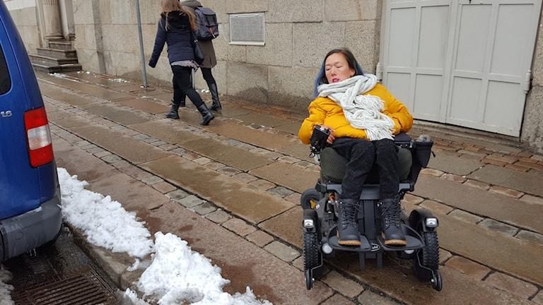 Sofia Jönsson i sin permobil på trottoaren.