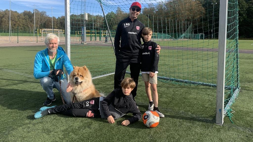 Två pappor och deras söner vid fotbollsplan.