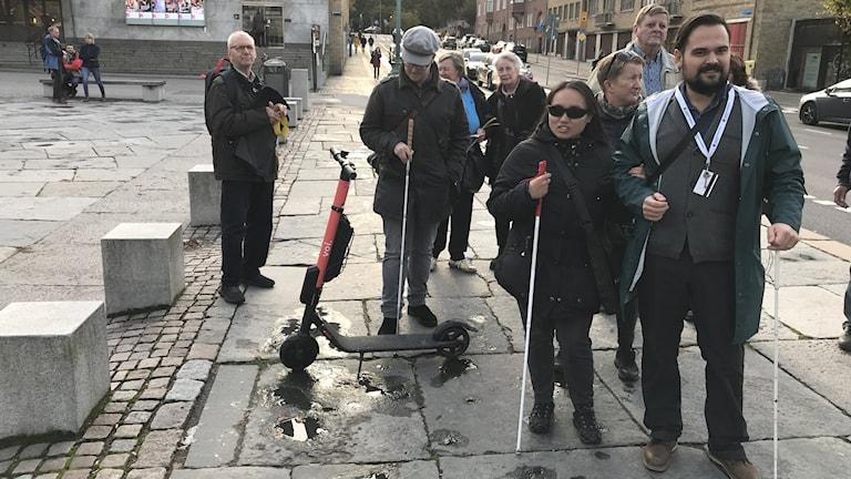 Personer med vita käppar står på gångbanan vid Götaplatsen.