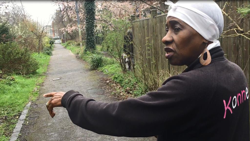 Patsy Mckies står på en gångväg i ett grönområde och pekar ut platsen där hennes son sköts till döds.