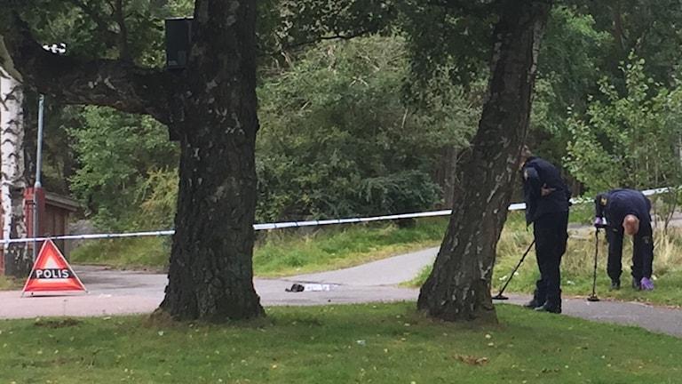 Två av polisens tekniker söker på marken.