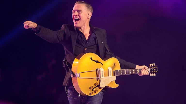 Bryan Adams står på scen med en gitarr och pekar mot publiken.