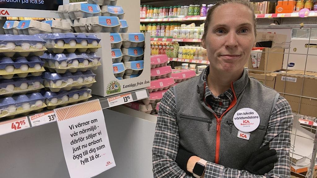 En kvinna står med korslagda armar intill en hylla med ägg.