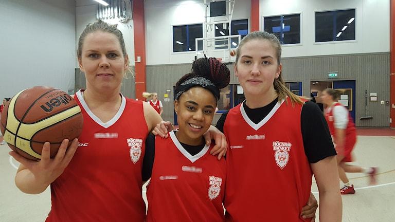Hanna Johansson, Fantasia Hilliard och Elin Ljungberg står på en basketplan där övriga laget tränar i bakgrunden. Hanna Johansson håller i en basketboll.