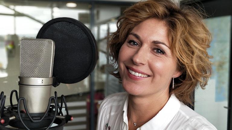 En kvinna med ljusbrunt hår och stort leende sitter framför en mikrofon i radiostudion.