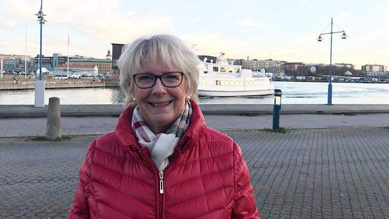 En kvinna i pensionsålder med grått hår, glasögon och röd täckjacka står vis älvkanten.
