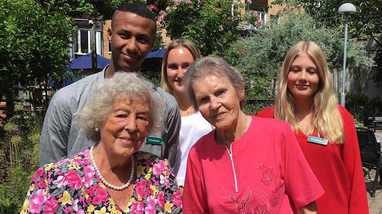 tre ungdomar tillsammans med två äldre kvinnor