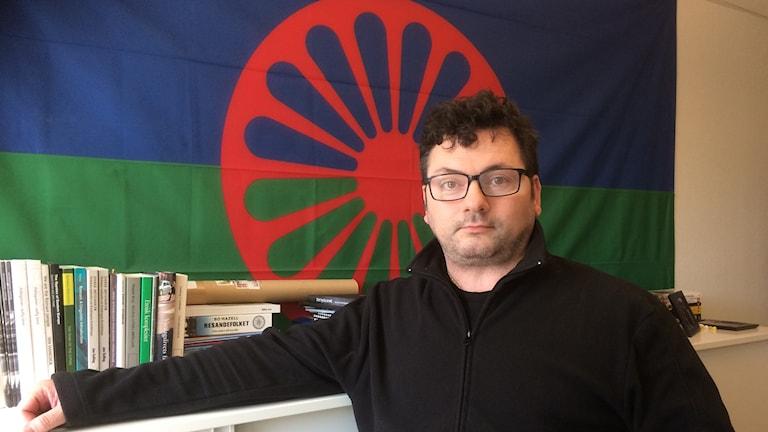 Domino Kai framför den blå-,röd- och grönfärgade romska flaggan.