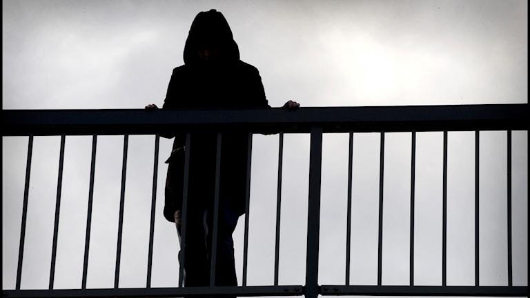 Kvinna som står vid räcke