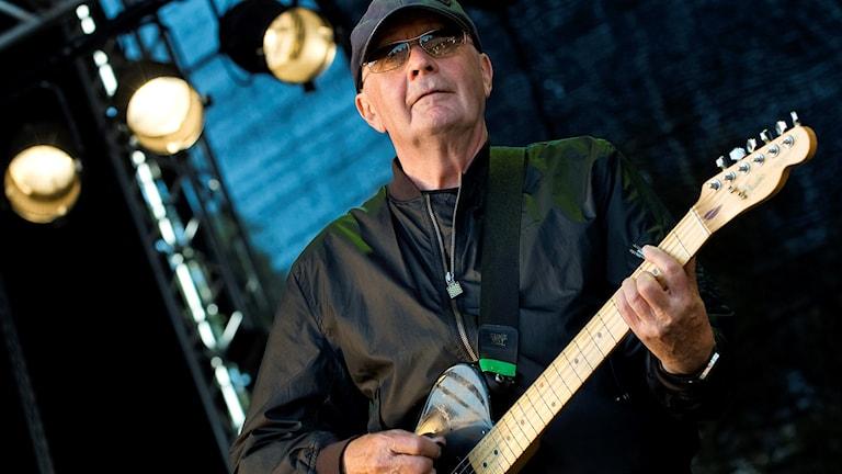 En äldre man i keps och solglasögon spelar elgitarr på en scen.