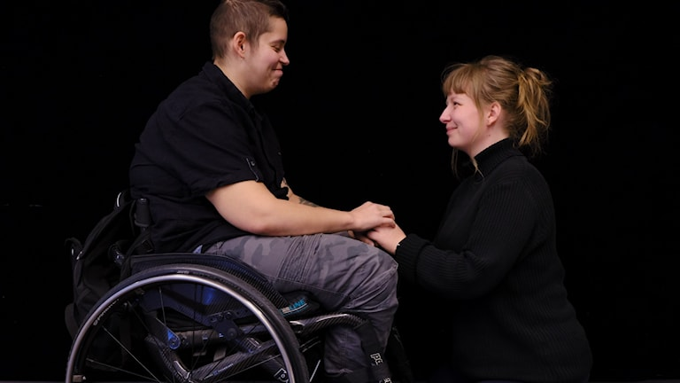 En tjej som sitter i rullstol och en tjej som sitter framför henne på knä håller i varandras händer.