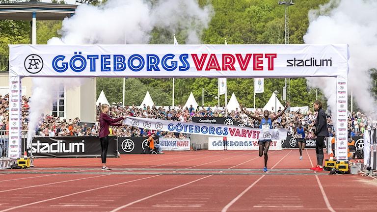 En löpare korsar mållinjen med armarna uppsträckta i segergest.