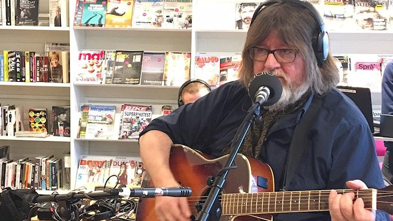 En man med långt hår och stort skägg spelar på en gitarr.