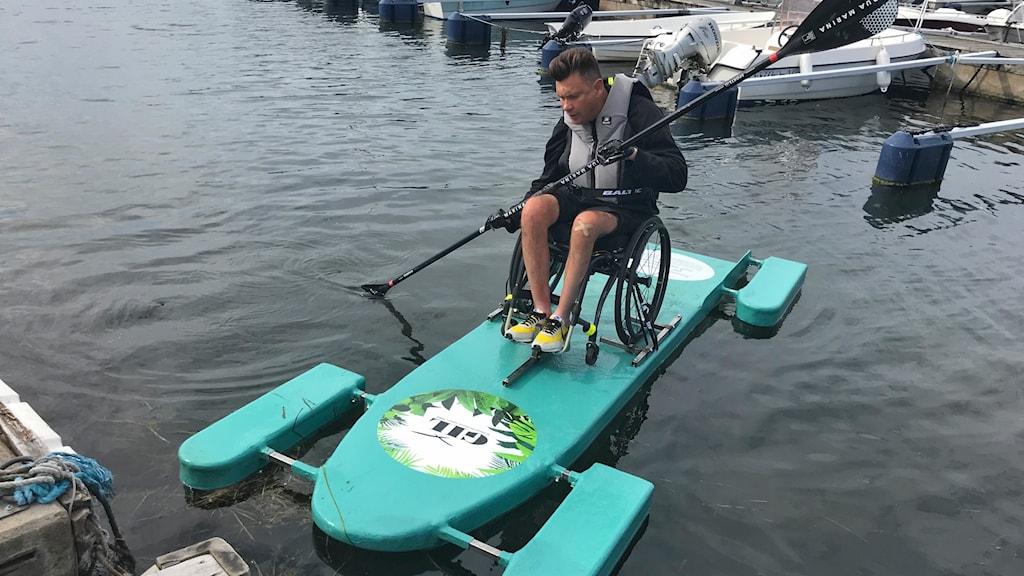 Rullstolsburen man sitter på sin paddleboard