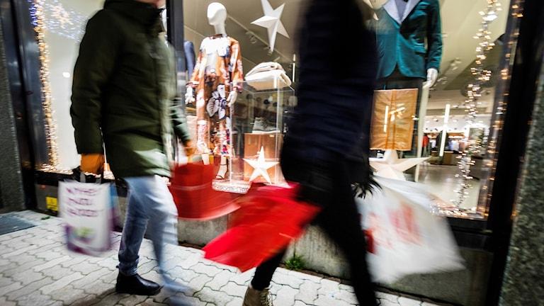 Personer som går med shoppingpåsar förbi ett skyltfönster.