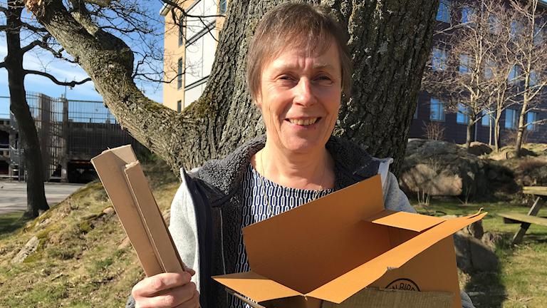 Medelålders kvinna håller upp kartonger framför träd