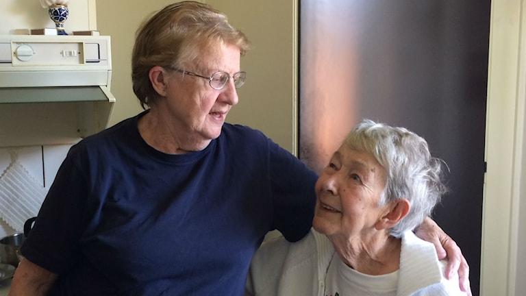 Två äldre kvinnor talar med varandra i ett kök