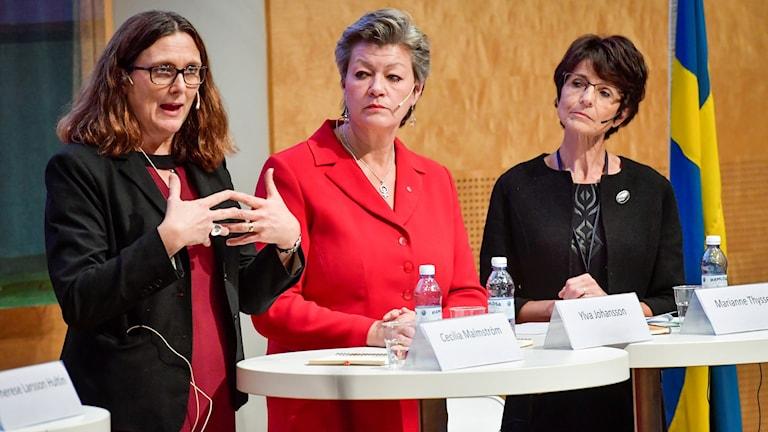 Tre kvinnor talar vid ett podium.