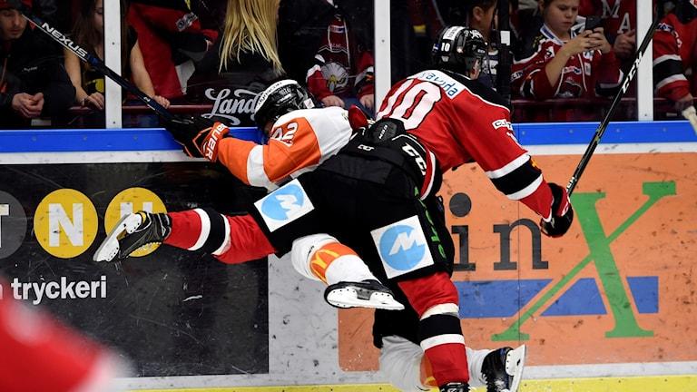 En Karlskronaspelare tacklas in i sargen av en Malmöspelare under en hockeymatch.