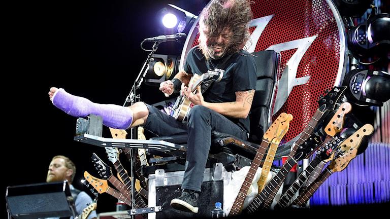 En man sitter med gipsat ben och spelar elgitarr