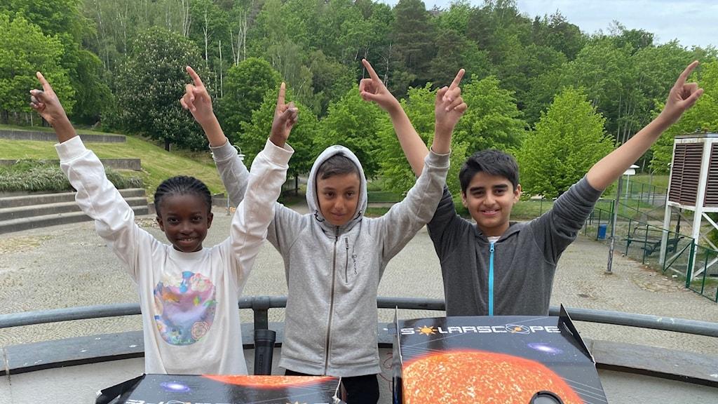 Tre elever framför ett rymdlabb.