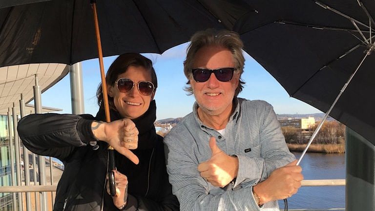 Peo och Matilda med paraplyer och solglasögon i solen utanför radiohuset.