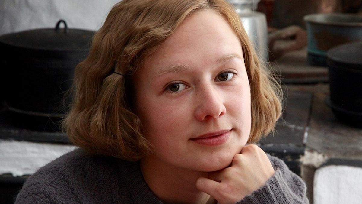 En ung kvinna tittar mot kameran.
