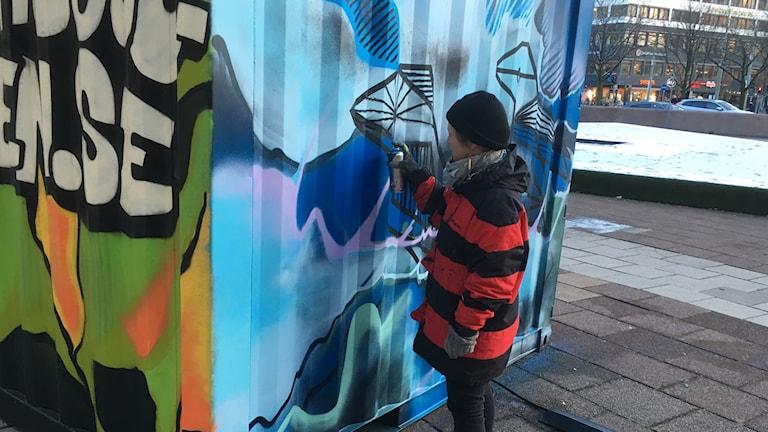Camilla sprayar containern med en av sina färgburkar